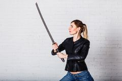 A young woman with a large sword stock photography