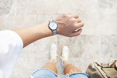 A young woman is late on time, in a hurry she checks the deadline on her classic watch. A young woman is late on time, in a  hurry she checks the deadline on her stock photography