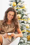 Young woman with latte macchiato in front of christmas tree Royalty Free Stock Photo