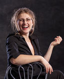 Young woman laughing. While sitting on chair. on dark background Stock Images