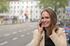 Young woman laughing as she chats on her mobile Royalty Free Stock Photography