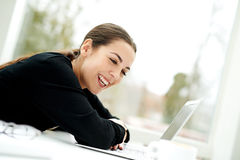 Young woman laughing as she reads her laptop Stock Photography
