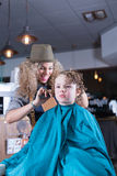 Young woman laughing while cutting boy hair Royalty Free Stock Images