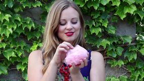 Young Woman Laughing and Eating Pink Cotton Candy With Ivy Background stock video