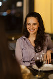 Young woman laughing with friends. Young woman laughing at a dinner with friends in a restuarant Royalty Free Stock Photos