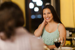 Young woman laughing with friends. Young women laughing at a dinner with friends in a restuarant Royalty Free Stock Photo