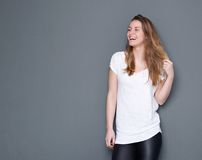 Young woman laughing with hand in hair Royalty Free Stock Images