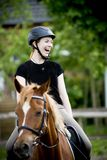 Young woman laughing on her horse Royalty Free Stock Image