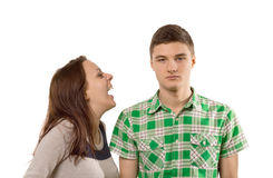 Young woman laughing at her own joke. Young women laughing at her own joke as he boyfriend stands looking unimpressed and unamused with a stony face, isolated on Royalty Free Stock Images