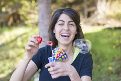 Young woman laughing and makes soap bubbles Stock Photos