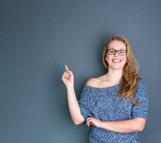 Young woman laughing and pointing finger. Close up portrait of a young woman laughing and pointing finger up on gray background Stock Images