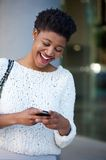 Young woman laughing and reading text message on cellphone Stock Photo