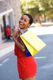 Young woman laughing with shopping bags outdoors Royalty Free Stock Image