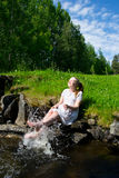 Young woman laughing and splashing. With hes feet in the water Stock Photos