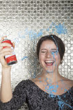 Young woman laughing and spraying party string over herself Royalty Free Stock Photography