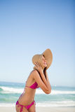 Young woman laughing while standing on the beach and holding her hat Stock Images