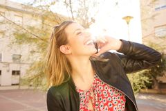 Young woman laughing and talking on cell phone outdoors Stock Image