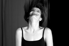 Young woman laughing and throwing her head back. Young, attractive, fit, healthy woman laughing and throwing her head back with long dark hair flying everywhere royalty free stock photography