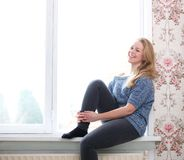 Young woman laughing by window Royalty Free Stock Images
