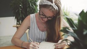 Young woman laughing, writing in notebook with card in her hand. Female student joking and learning stock video