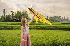 Young woman launches a kite in a rice field in Ubud, Bali Island, Indonesia royalty free stock photography