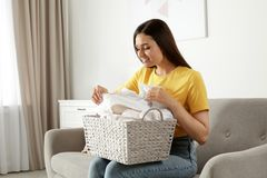 Young woman with laundry basket full of clean towels on sofa stock images