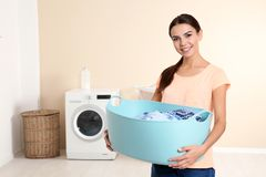 Young woman with laundry basket near washing machine at home stock photography