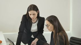 Pretty businesswomen are talking in the office. Young woman lawyer in glasses sits at the table in the office and talks with her colleague, who`s sitting on stock video footage