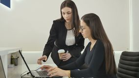 The lawyers are working in the office. Young woman lawyer sits at the table in the office and talks with her colleague, who`s sitting on table. One of the women stock video