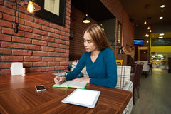 Young woman lawyer is using digital table,. Young woman  entrepreneur dreaming about something good while working on net-book and writing in a notebook Royalty Free Stock Photo