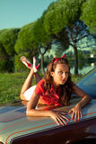 Young woman lay on retro car in summer sunset Royalty Free Stock Image