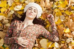 Young woman laying in the autumn leaves Stock Photos