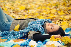 Young woman. Laying in autumn leaves royalty free stock photo
