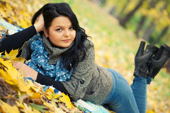 Young woman. Laying in autumn leaves royalty free stock photos