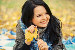 Young woman. Laying in autumn leaves stock photo