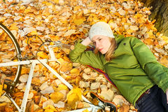 Young woman laying in autumn leaves royalty free stock image