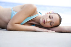 A young woman laying on the beach Stock Image