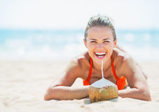Young woman laying on beach with coconut Stock Image