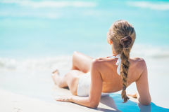 Young woman laying on beach. rear view Stock Photos