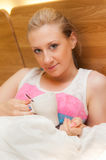 Young Woman Laying in Bed Holding a Cup Royalty Free Stock Image