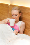 Young Woman Laying in Bed Holding a Cup Royalty Free Stock Photography