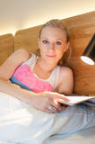 Young Woman Laying in Bed Reading a Magazine Stock Image