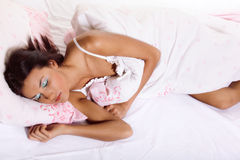 Young woman laying on the bed. Young woman laying and sleeping on the bed royalty free stock images