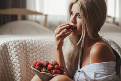 Young woman laying on bed with strawberry Royalty Free Stock Photography