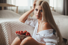 Young woman laying on bed with strawberry Stock Image