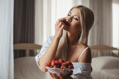 Young woman laying on bed with strawberry Royalty Free Stock Photo