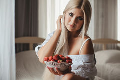Young woman laying on bed with strawberry Royalty Free Stock Images