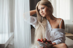 Young woman laying on bed with strawberry Stock Photos