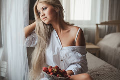 Young woman laying on bed with strawberry Stock Photo