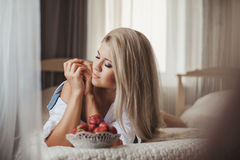 Young woman laying on bed with strawberry Royalty Free Stock Image